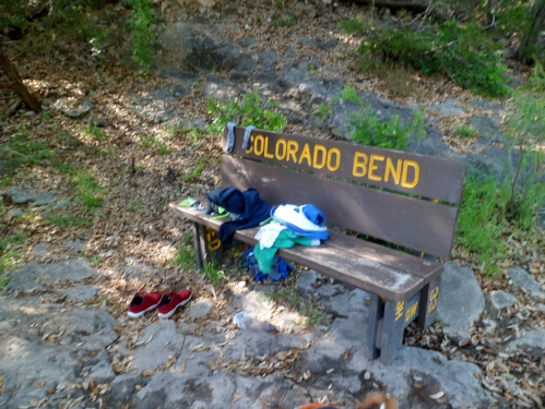 Clothes on the bench by swimming hole