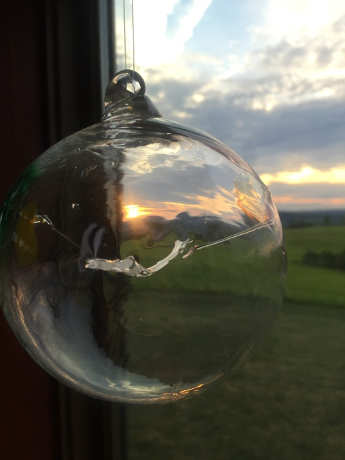 Sunset through a glass sculpture hanging in the window